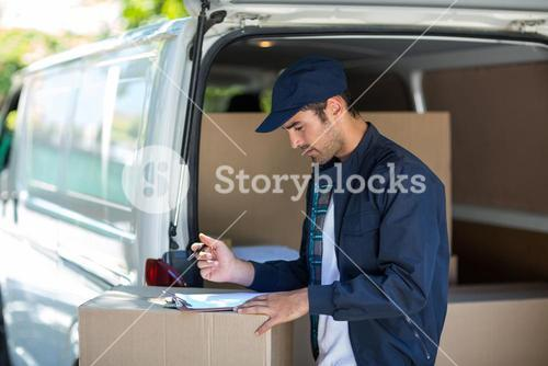 Side view of delivery person writing in clipboard
