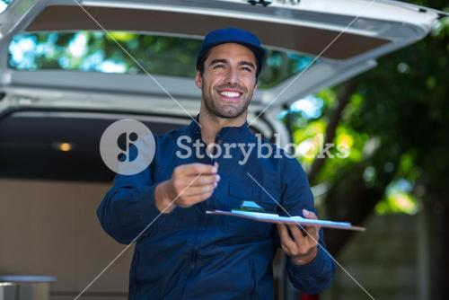 Smiling delivery person giving clipboard for signature