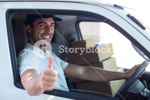 Delivery man showing thumbs up while driving van