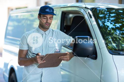 Delivery person looking at clipboard