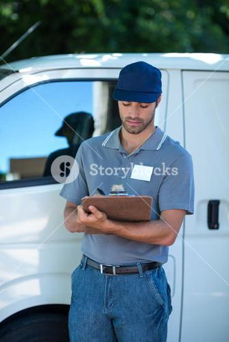 Delivery person writing in clipboard