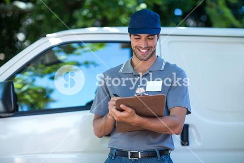 Smiling delivery person writing in clipboard