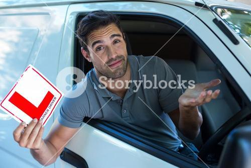 Handsome man shrugging while holding L plate