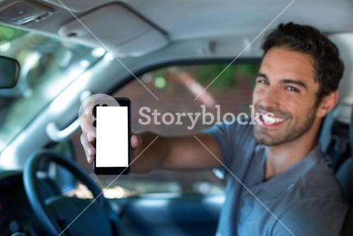 Handsome man holding phone in car