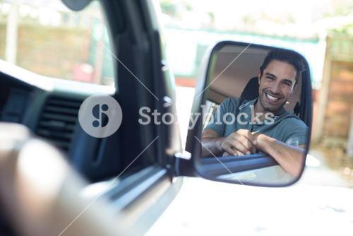 Handsome man sitting in car on mirror