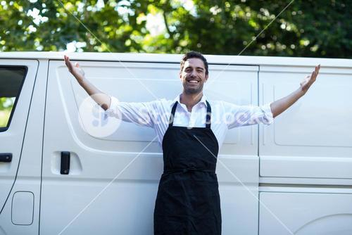 Portrait of confident delivery man with arms outstretched