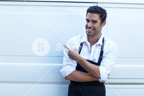 Portrait of confident delivery man pointing
