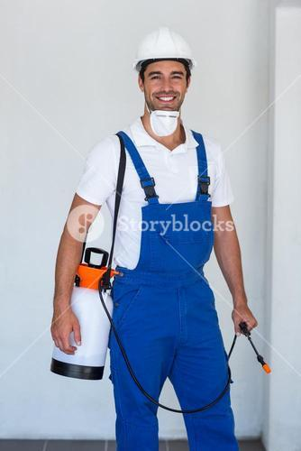 Portrait of happy manual worker with insecticide