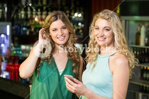 Smiling friends using smartphone