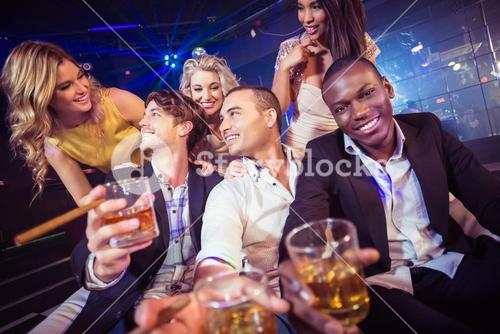 Happy friends holding a glass of alcohol