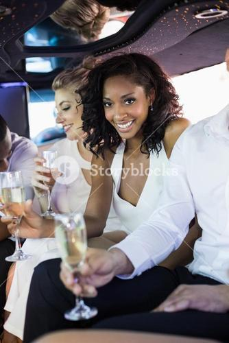 Well dressed woman drinking champagne in a limousine
