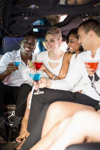 Well dressed people drinking cocktails in a limousine