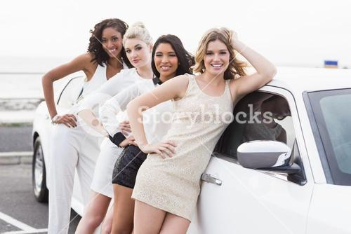 Well dressed women posing leaning on a limousine