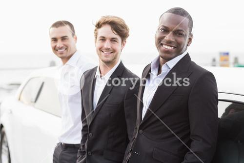 Well dressed men posing leaning on a limousine