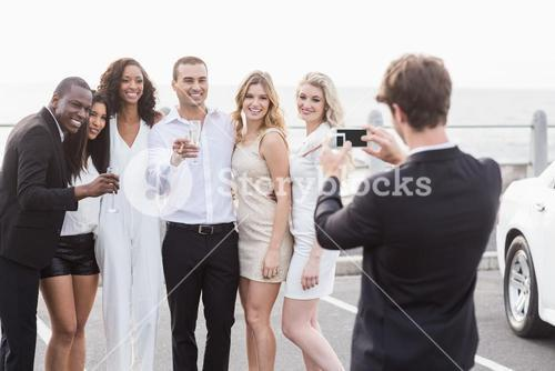 Well dressed people taking pictures next to a limousine