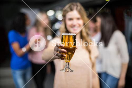 Smiling girl showing a beer with her friends