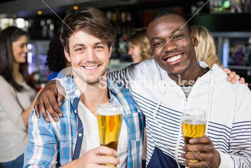 Smiling friends showing beer with their friends