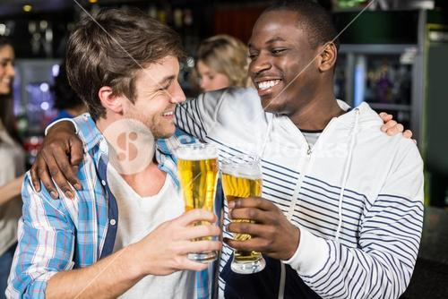Smiling friends tasting with beer with their friends