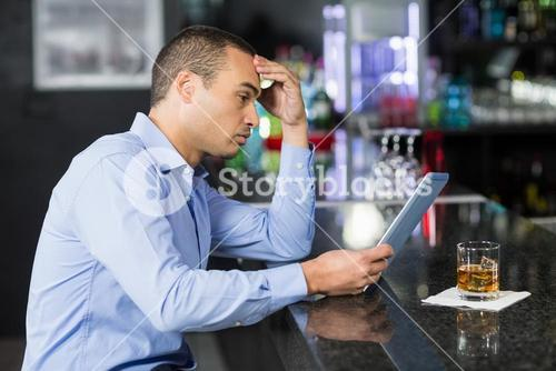 Businessman having a whisky and using laptop