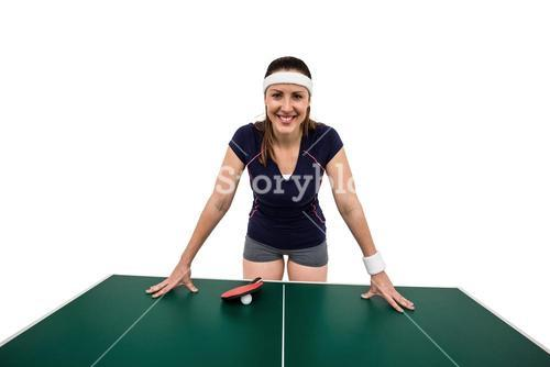 Happy female athlete leaning on hard table