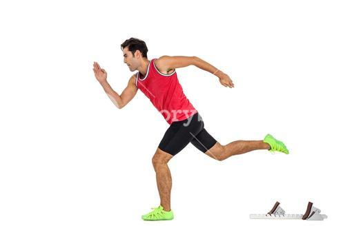 Confident male athlete running from starting blocks