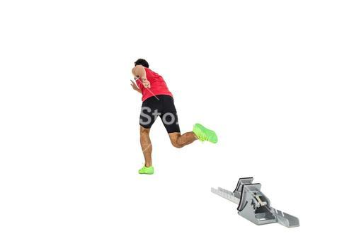Male athlete running from starting blocks