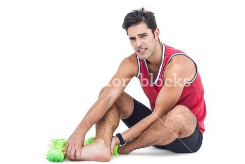 Portrait of male athlete with foot pain on white background