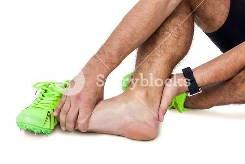 Male athlete with foot pain on white background