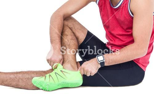 Male athlete wearing his sport shoes and getting ready for sport