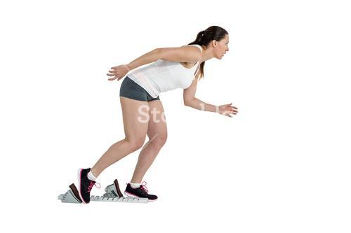 Confident athlete woman running from starting blocks
