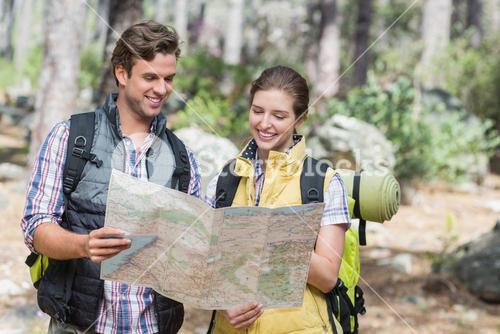 Young couple planning with map while hiking