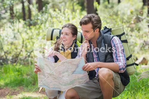 Couple crouching and planning with map