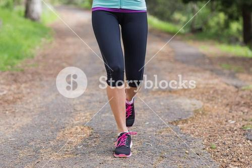 Low section of woman running on footpath