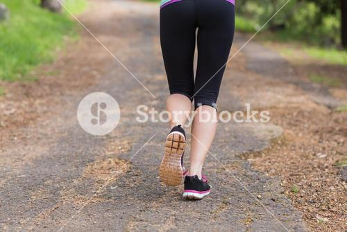 Low section of jogger running on footpath