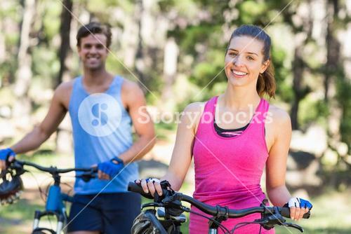 Woman and man with bicycles in forest