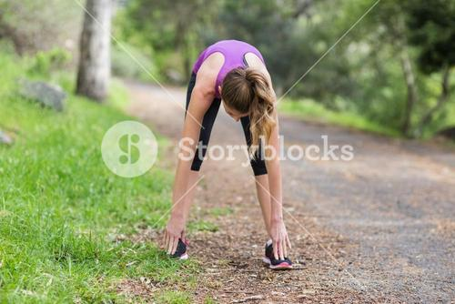 Young woman exercising on footpath