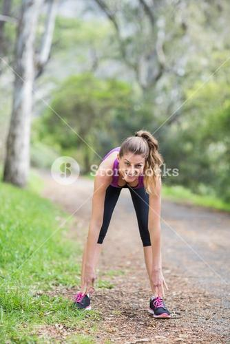 Young woman bending on footpath