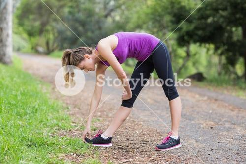 Side view of woman exercising on footpath