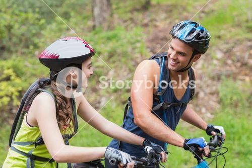 Young couple with bikes looking at each other