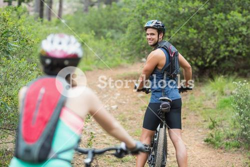 Happy biker looking at woman in forest