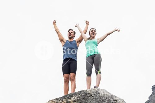 Young couple with arms raised on rock against sky