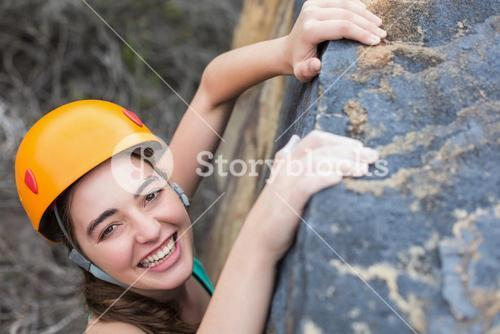 High angle view of smiling woman climbing rock