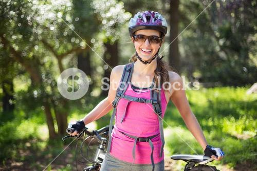 Portrait of joyful woman standing at forest