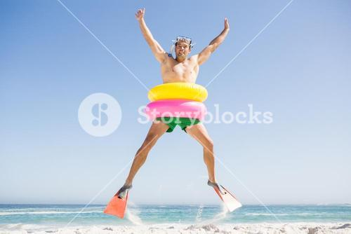 Smiling man jumping with rubber ring