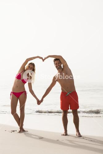 Couple forming a heart with arms