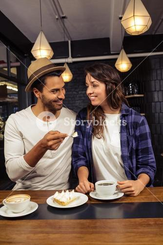 Man feeding woman with a piece of cake