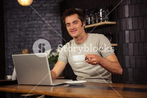 Man using a laptop and drinking coffee