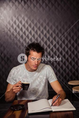 Hipster having coffee and writing in planner