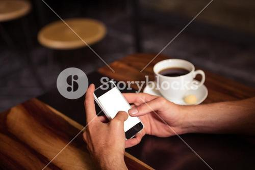 Hipster man using smartphone while drinking coffee