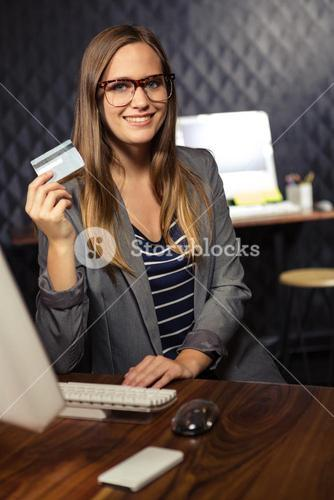 Creative businesswoman showing a credit card